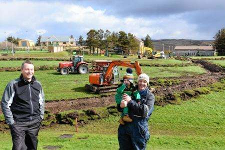 Murdo Gordon and Alan Matheson of Bettyhill FC (along with young Zac) looking over the park as work goes ahead.