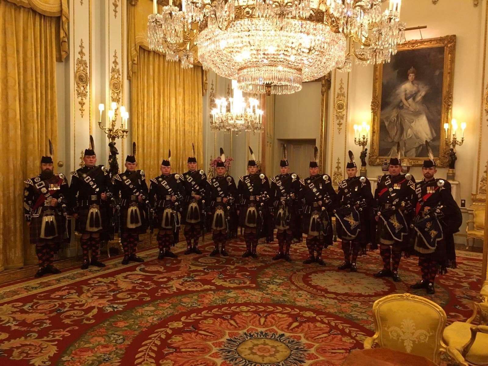 Pipe Major Colin Simpson stands far left at Buckingham Palace while Norman Gillies is fourth left and Hugh Mackay third right.